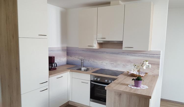 Blick in die Küche mit Kaffeemaschine, Spüle, Herd