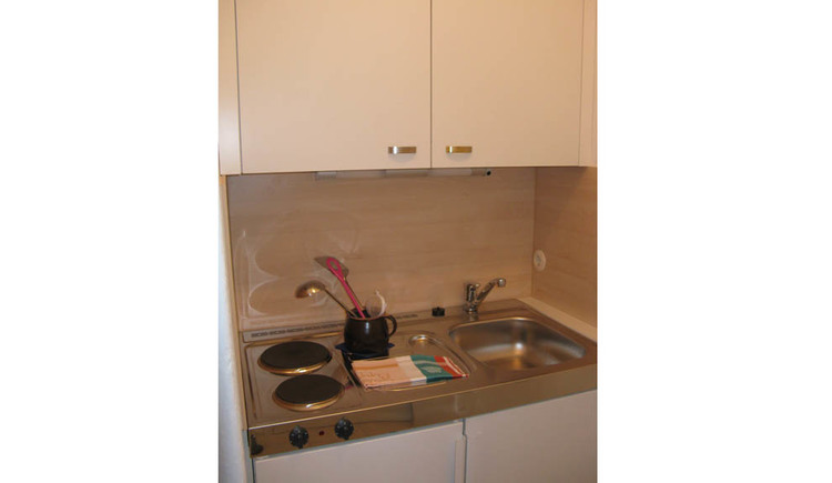 Small cooking facilities with stove tops, dishwashing and cabinets, kitchen utensils stand in a bowl