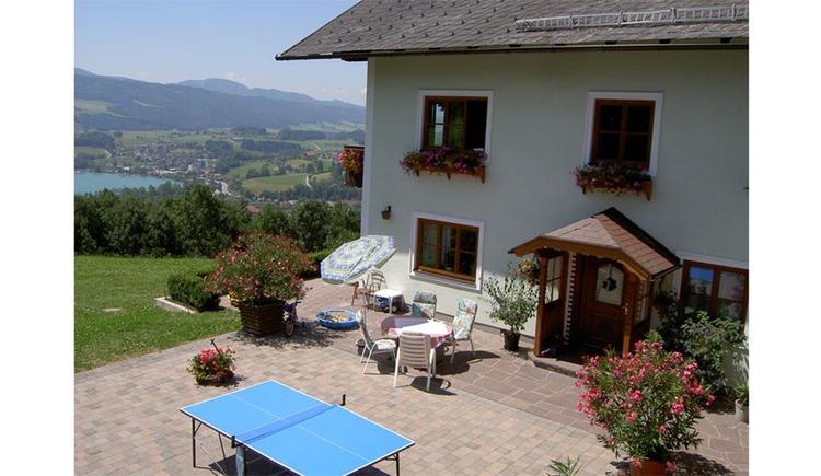 Blick auf das Haus, davor Tisch und Stühle, Sonnenschirm, Pflanzen, Tischtennistisch, im Hintergrund Wiesen, Bäume, See