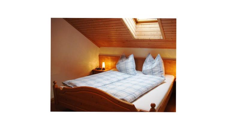 Schlafzimmer mit Doppelbett, Tischlampe, Dachfenster