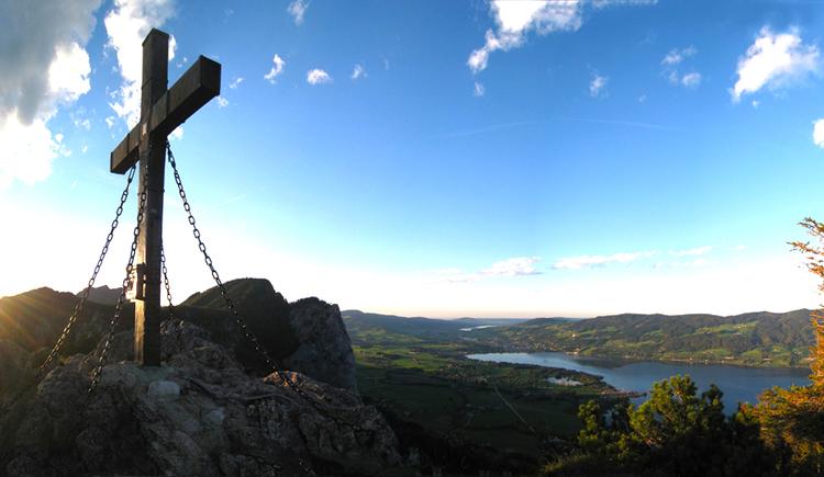 Blick auf ein Kreuz am Berggipfel, im Hintergrund ein See
