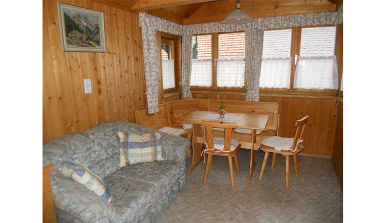 Wohn- und Essbereich mit einer Couch, im Hintergrund Eckbank mit Tisch und Sesseln, Fenster