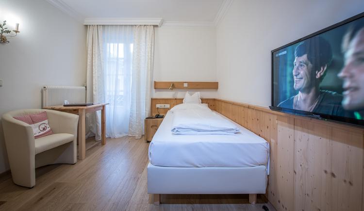 Zimmer mit Einzelbett und Flachbild TV an der Wand sowie Tisch und Sessel