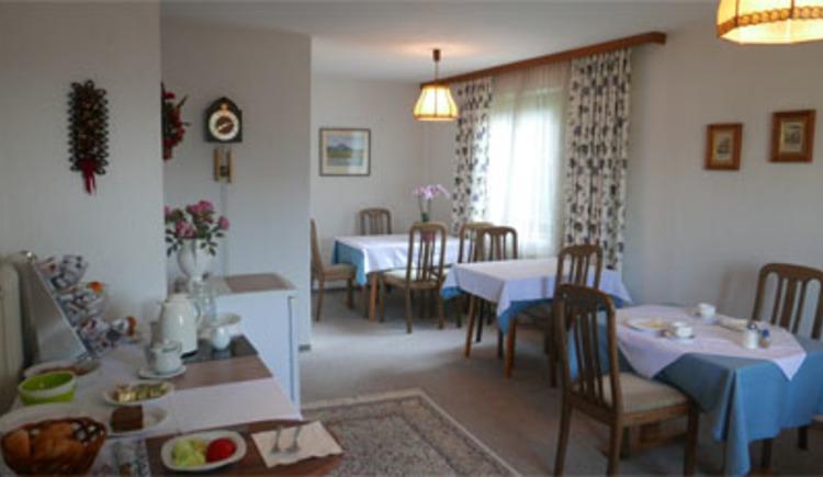 seitlich gedeckte Tische und Stühle, im Hintergrund ein Fenster, seitlich Frühstücksbuffet