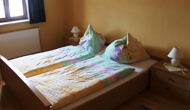 Schlafzimmer mit Doppelbett, Nachtkästchen, Tischlampen, seitlich ein Fenster