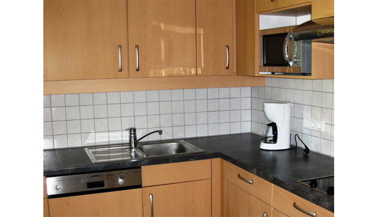 Kitchen with sink, dishwasher, coffee maker, microwave, stove