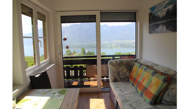Couch, Tisch, im Hintergrund große Balkontür mit Blick auf den See