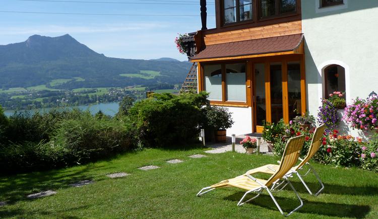 Ausblick von der Wiese, auf die Sträucher, im Hintergrund der See und die Berge, seitlich Liegestühle und ein kleiner Teil vom Haus