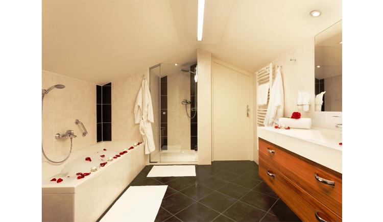Badezimmer mit Badewanne, Dusche, Handtuchtrockner, Waschbecken