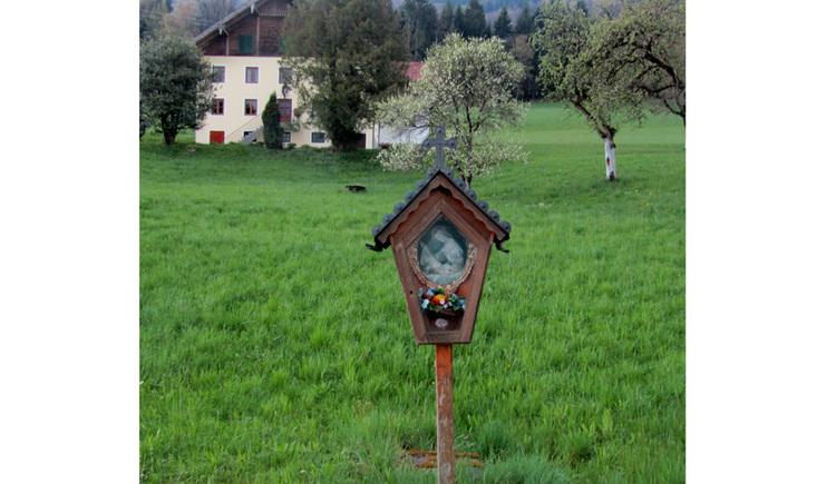 Blick auf den Holzbildstock mit einem Heiligenbild, Blumen, im Hintergrund Wiesen, Bäume und ein Haus