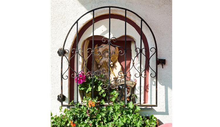 hinter Gitter befindet sich eine Heiligenfigur, davor Blumen