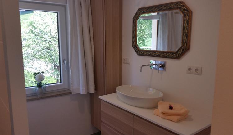 Waschbecken, Spiegel, seitlich ein Fenster