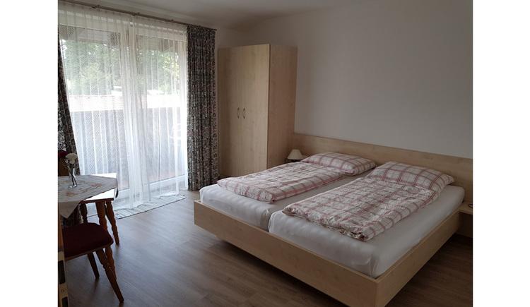 Doppelbett, Kleiderschrank, seitlich eine Balkontür
