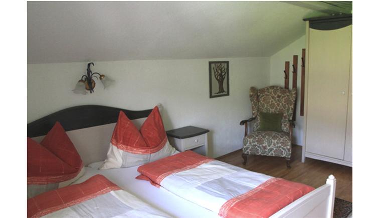 Schlafzimmer mit Doppelbett, Nachtkästchen, gemütlicher Sessel, Kleiderschrank
