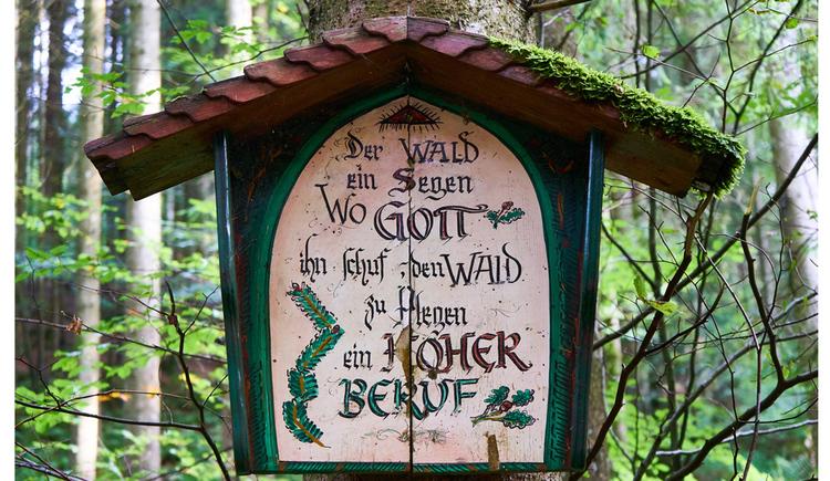 Blick auf das in Holz-gerahmte Bild mit einer Aufschrift, im Hintergrund ein Wald