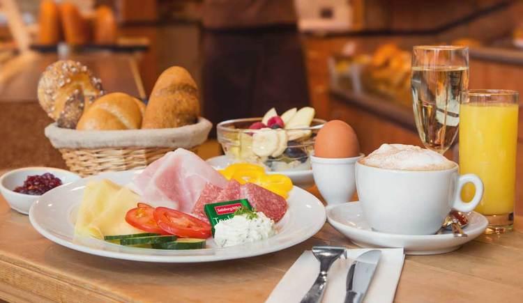 Im Bild sieht man ein typisches Frühstück, mit Gebäck, Orangensaft, Kaffee, Ei, Sekt, Marmelade, Wurst, Käse und Gemüse. (© Obauer)