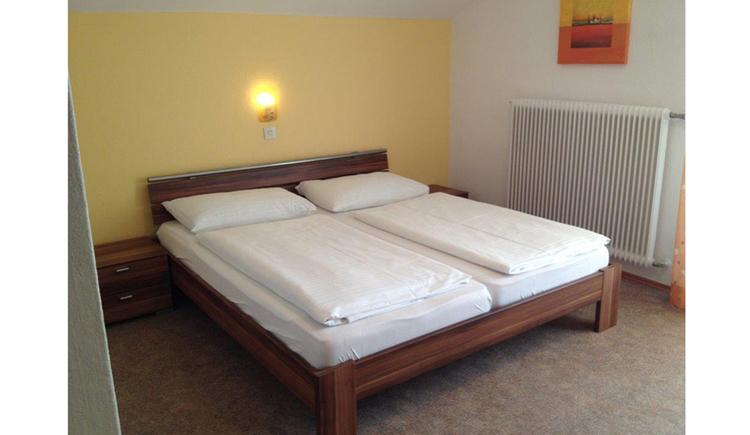 Schlafzimmer mit Doppelbett, Nachtkästechen, seitlich im Hintergrund Heizkörper, Bild an der Wand