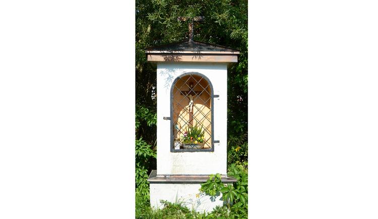 Blick auf den Bildstock, hinter Gitter ein Kreuz und Blumen, im Hintergrund Sträucher und Bäume