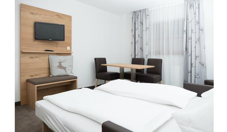 Doppelbett, seitlich ein Fernseher an der Wand, im Hintergrund Tisch mit Stühlen, Fenster
