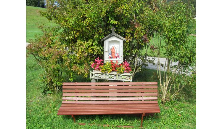 Hinter einer Holzbank befindet sich ein Bildstock mit einer Heiligenfigur, Blumen, im Hintergrund Sträucher
