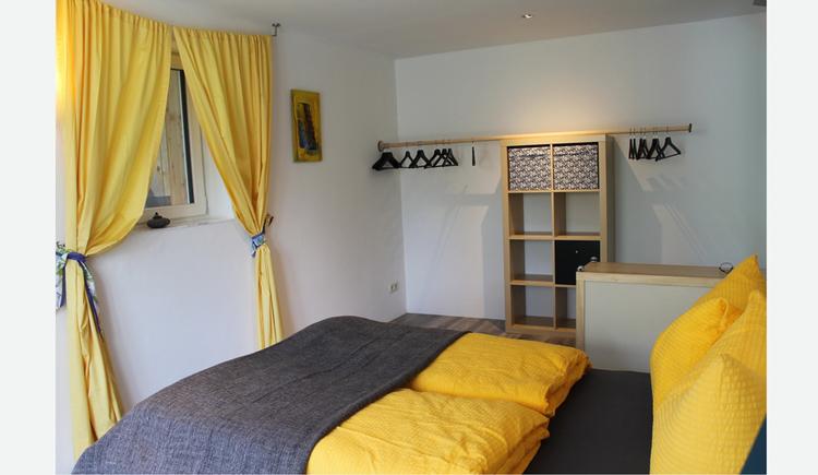 Doppelbett, im Hintergrund ein Regal, Kleiderhaken, seitlich ein Fenster