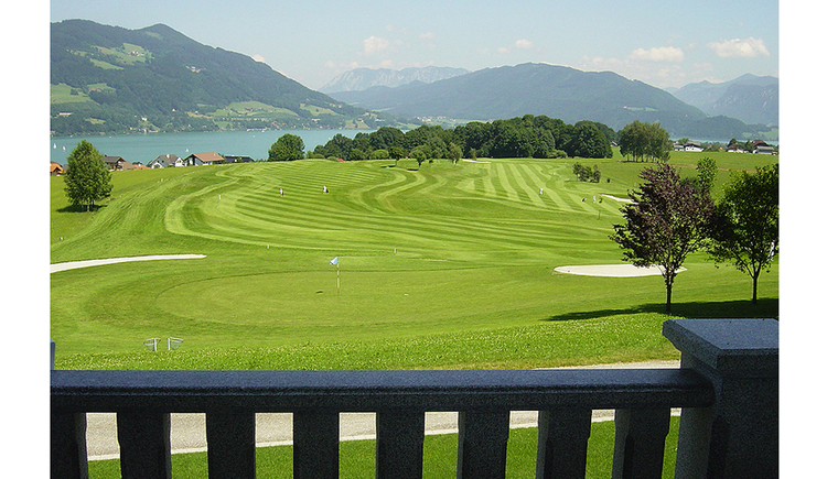 View from the balcony to the golf course, in the background the lake and the mountains