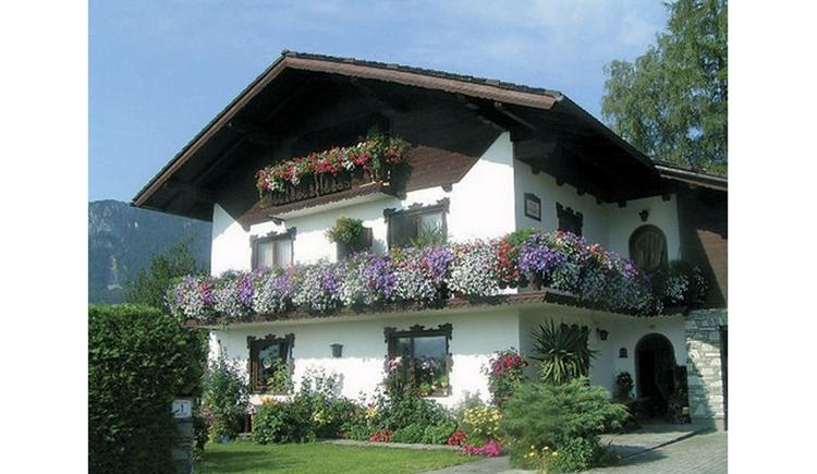 Blick auf das Haus mit Balkon und Blumen, im Vordergrund ein Garten