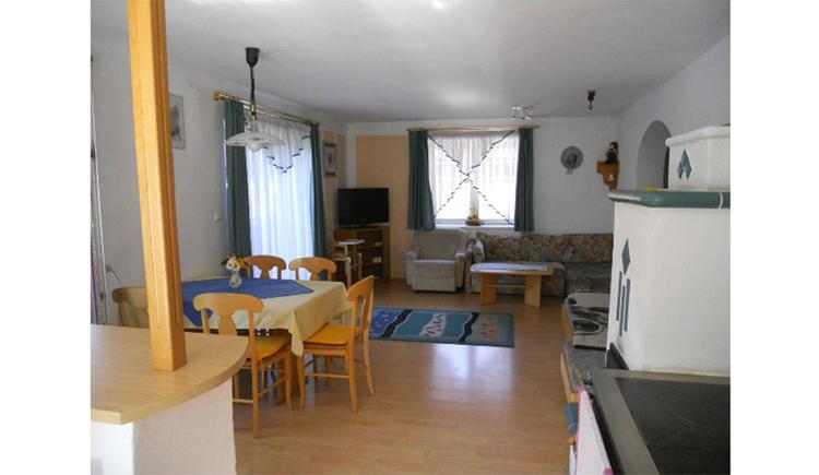 Wohnbereich, seitlich Tisch mit Stühle, Balkontür, im Hintergrund Fernseher, Fenster, Sessel, Couch, kleiner Tisch, Kachelofen