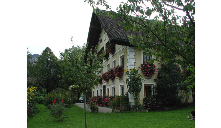 View of the house from the side, with flowers, in front of the house trees and shrubs. (© Strobl)