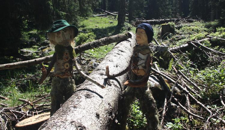 Einige Holzknechtwichtel arbeiten an gefällten Bäumen.