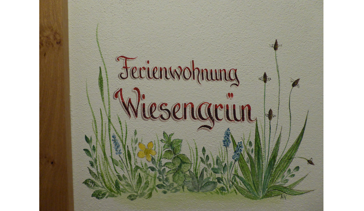 "Wallpainting with flowers and the writing ""Ferienwohnung Wiesengrün\"""