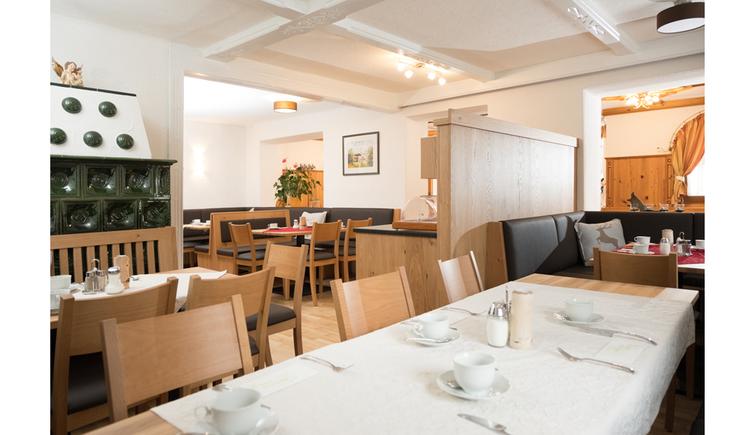 Blick auf gedeckte Tische, Stühle, seitlich ein Kachelofen
