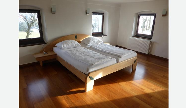 Doppelbett, im Hintergrund und seitlich Fenster