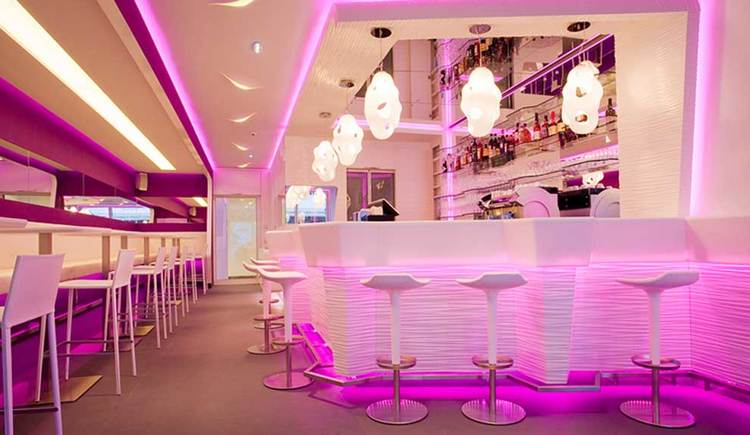 Innenraum mit einigen Stühlen und Tischen, auf der einen Seite befindet sich die Bar