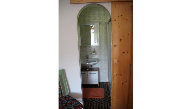 im Hintergrund Waschbecken, Spiegel, Unterschrank