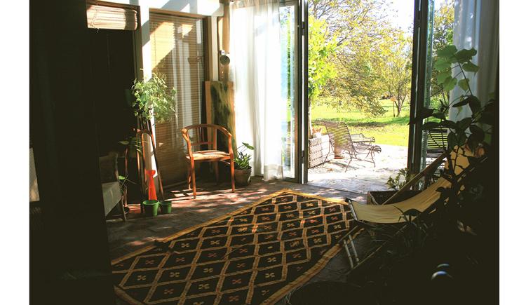 Blick aus dem Wintergarten mit Stühlen, Liegestuhl, Pflanzen, Teppich in den Garten mit Bank, herrlicher Blick auf die Wiesen und Bäume
