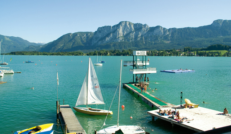 View from balcony of the lake, the jump tower, the bridge, sailboat, in the background the mountains