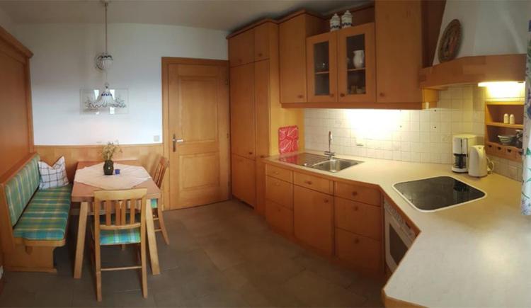 seitlich eine Küche mit Her, Kaffeemaschine, Tisch, Eckbank, Stühle, im Hintergrund eine Tür
