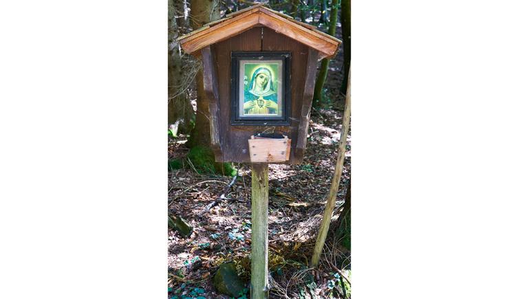 Blick auf ein Holztaferl in einem Wald, Heiligenbild