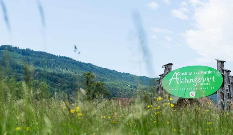 look at the sign with the logo of hotel Aichingerwirt, flower meadow in the foreground, mountains in the background. (© Aichingerwirt)