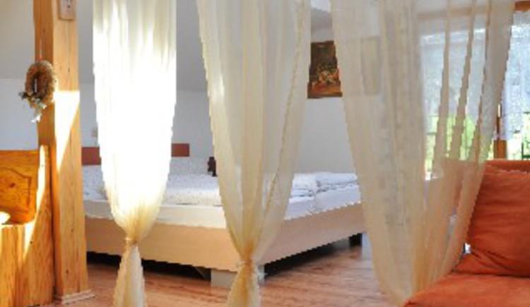 """Haus Schober: Der Wohn- und Schlafbereich der Fewo \""""B\"""" wird durch einen Vorhang getrennt."""