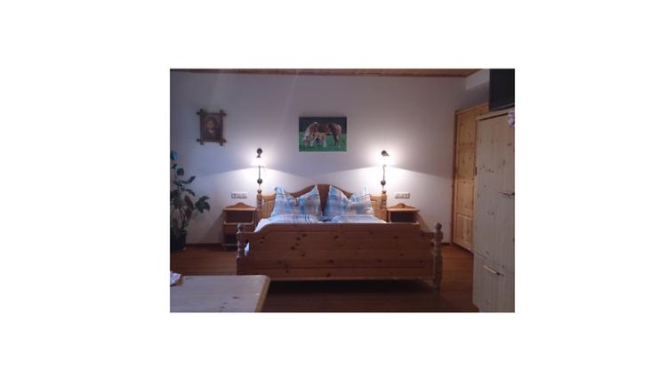 Schlafzimmer mit Doppelbett, Nachtkästchen, seitlich ein Kleiderschrank