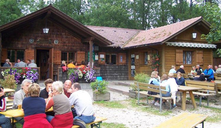 Pettenfirsthütte mit Tischen und Bänken vor der Hütte