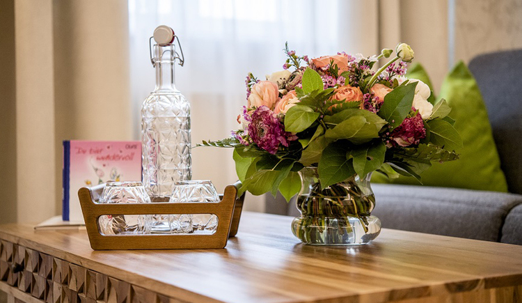 Glass bottle and glasses on a table, bouquet in a vase. (© Karin Lohberger)