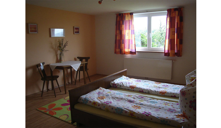 Bedroom with double bed, side table with chairs, in the background a window
