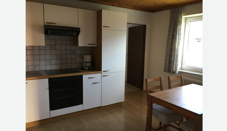 Kitchen with stove, coffee machine, side table with chairs, window
