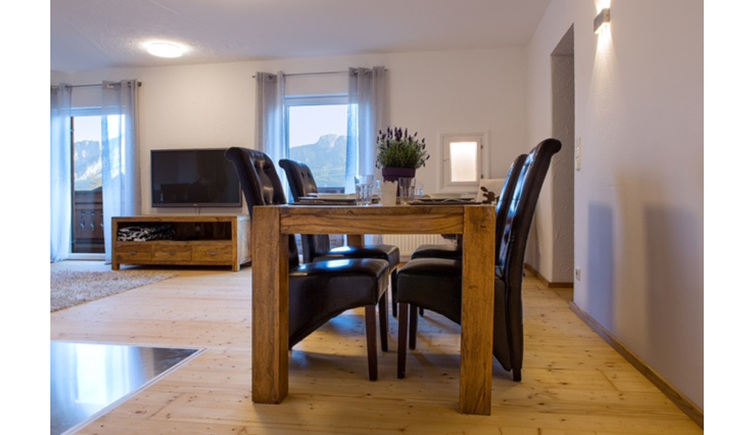 Table with chairs, in the background chest of drawers with a TV