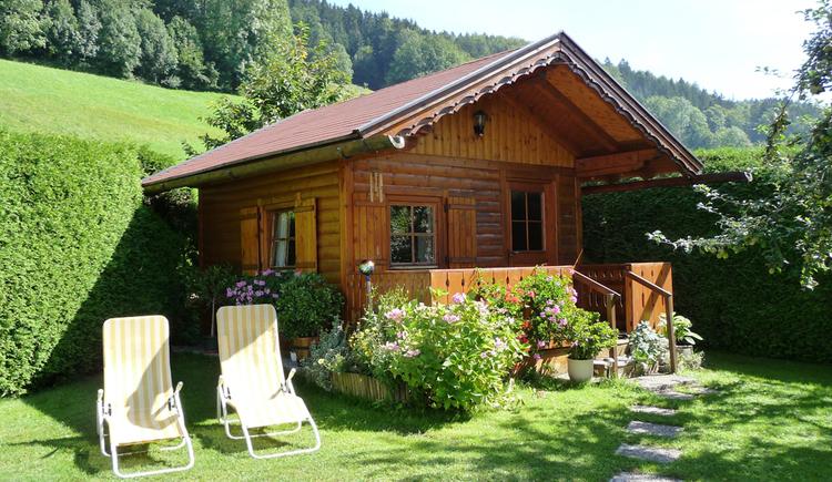 Blick auf das Holzgartenhaus, im Vordergrund Liegestühle, Blumen/Sträucher, im Hintergrund Wiese und Wald