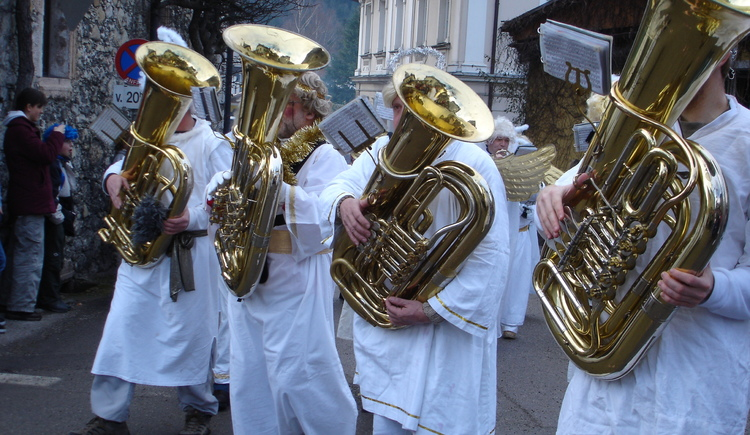 Four musicians of brass band Bürgermusik Bad Goisern with instruments - encased as an angel.