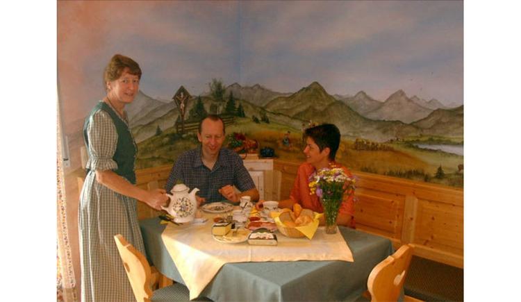 Personen beim gedeckten Frühstückstisch